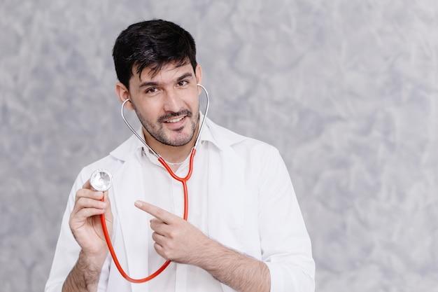 Apuesto médico mano apuntando al estetoscopio para pedir un control saludable o recordar el concepto de tratamiento con medicamentos