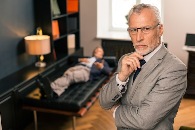 Apuesto médico serio pensativo de pie junto a su paciente mientras apoya su barbilla y mira frente a él