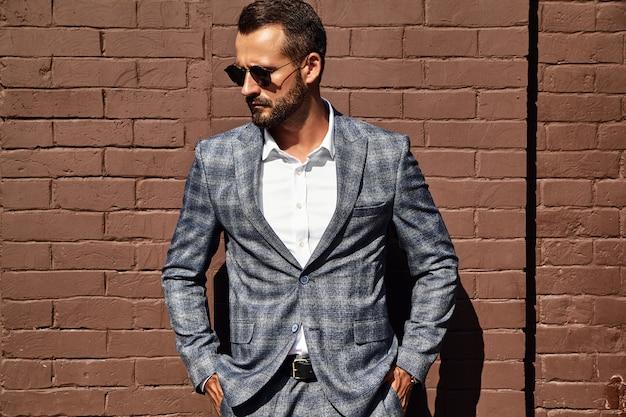 Apuesto modelo de empresario de moda vestido con elegante traje a cuadros posando junto a la pared de ladrillo en la calle