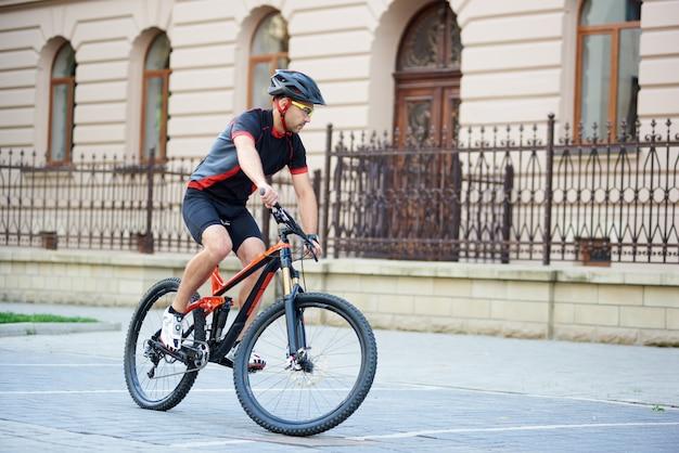 Apuesto motorista en ropa de ciclismo profesional y casco montando bicicleta cerca de hermosos edificios.