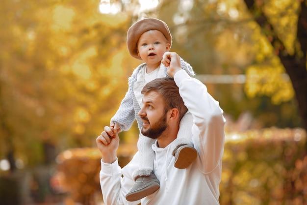 Apuesto padre en un suéter gris jugando con pequeña hija en un parque de otoño