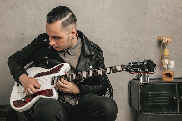 Apuesto rockero tocando la guitarra eléctrica