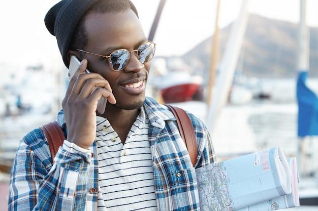 Apuesto viajero masculino elegante con mochila y guía de la ciudad hablando por teléfono móvil con su esposa después de la excursión, compartiendo buenas impresiones y emociones. personas, tecnología moderna y concepto de viaje.