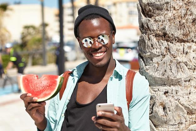 Apuesto viajero negro despreocupado con ropa urbana elegante posando para selfie, de pie al aire libre con una rodaja de sandía, recostado en la palmera, la pantalla del teléfono se refleja en sus lentes con espejos
