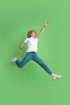 Apuntando hacia arriba en salto. retrato de mujer joven caucásica aislado en la pared verde. modelo de mujer hermosa en camisa blanca. concepto de emociones humanas, expresión facial, juventud.