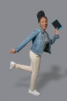 Apurado. imagen de una mujer joven de piel oscura corriendo y sosteniendo una tableta