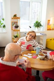 Aquí es. agradable anciana mirando sus cartas mientras está listo para vencerlos