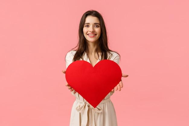 Aquí mi amor para ti. encantadora tierna y seductora, romántica joven dando una gran tarjeta de corazón, sonriendo encantada, expresando su afecto y admiración, de pie en la pared rosa