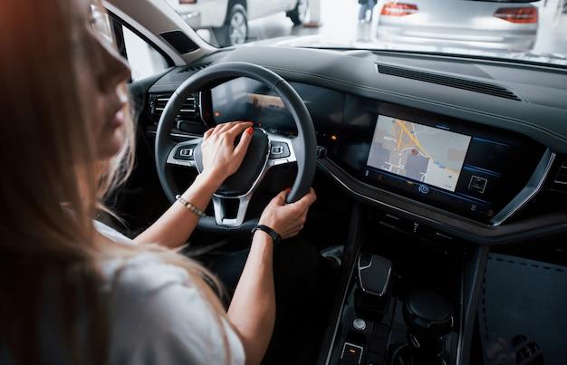 Aquí vamos. chica en coche moderno en el salón. durante el día en interiores. comprar vehículo nuevo