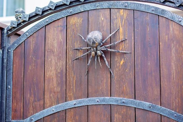 Una araña de hierro forjado decora la puerta. decoración del hogar de halloween. encanto en la puerta de entrada a la mansión.