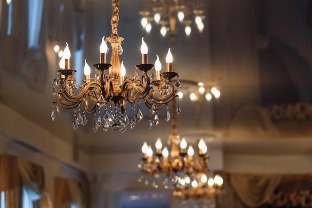 Araña de lujo vintage colgada en el techo con luces brillantes