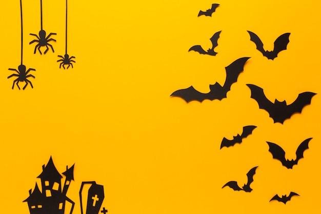Arañas de halloween y murciélagos con fondo naranja