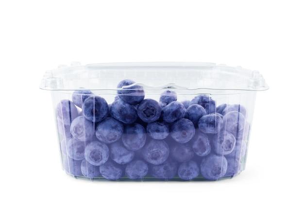 Arándanos frescos en recipiente de plástico aislado sobre fondo blanco.