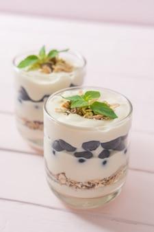 Arándanos frescos y yogur con granola - estilo de comida saludable