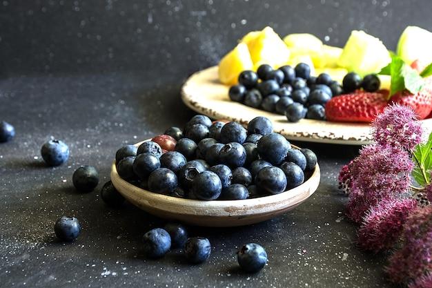 Arándanos y otra variedad de frutas sobre fondo oscuro
