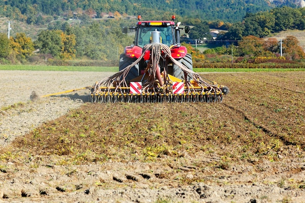 Arando el tractor pesado durante el cultivo agrícola trabaja en el campo con arado