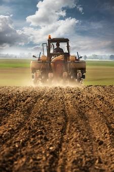 Arar y sembrar campo de maíz con tractor.