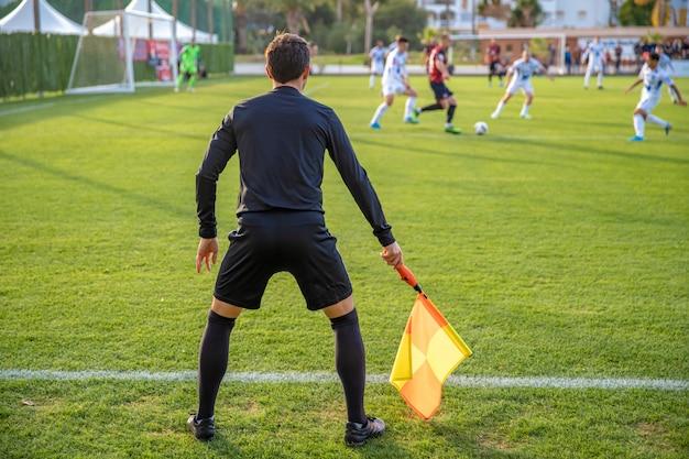 Árbitro asistente en un partido de fútbol viendo el partido