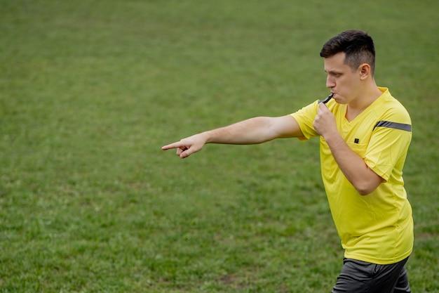 Árbitro que muestra la penalización mientras juega.