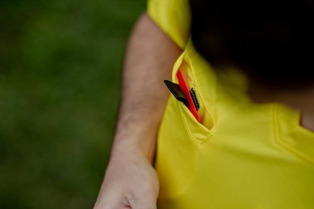Árbitro que muestra una tarjeta roja a un fútbol o jugador de fútbol disgustado mientras juega
