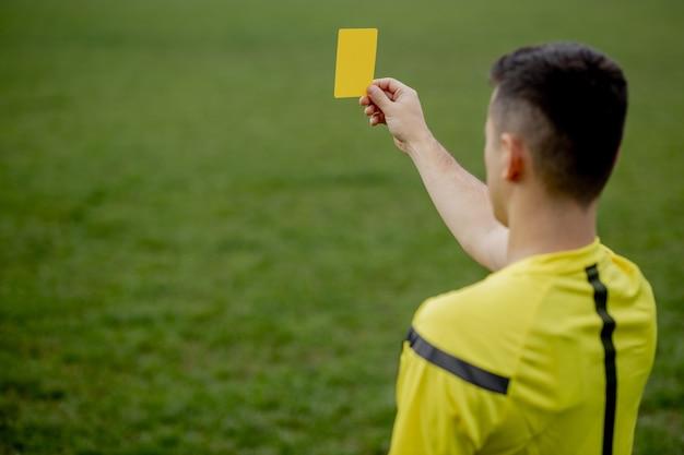 Árbitro que muestra una tarjeta roja a un futbolista o jugador de fútbol disgustado mientras juega.