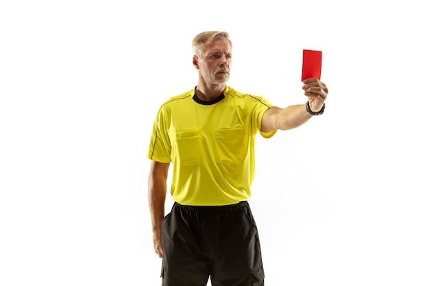 Árbitro que muestra una tarjeta roja a un jugador de fútbol o fútbol disgustado mientras juega aislado en la pared blanca.