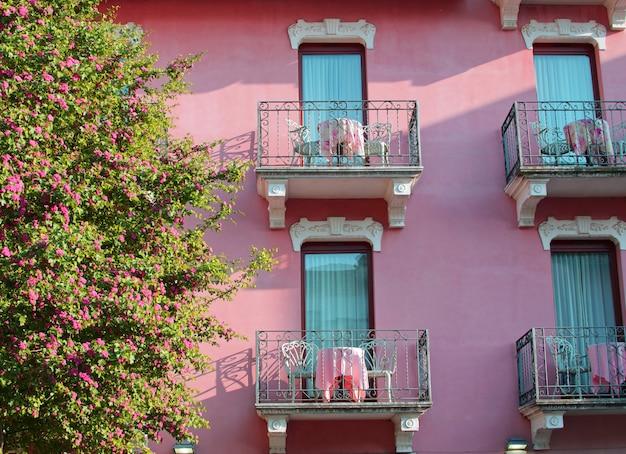 Árbol en flor y hermosa casa rosa con balcones en sirmione