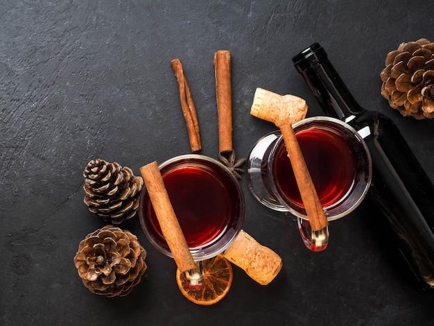 Árbol de mandarinas y ramitas con dos copas de vino caliente caliente con naranjas y especias.