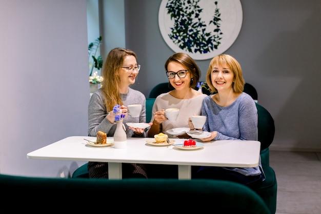 Árbol mujeres bonitas jóvenes mejores amigos. tiro horizontal de hermosas mujeres hablando y divirtiéndose mientras bebe café y come postres en la cafetería. amigas cotilleando durante la hora del café.