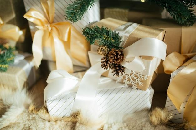 Árbol de navidad con adornos rústicos, cajas de regalo hechas a mano y regalos debajo en loft.