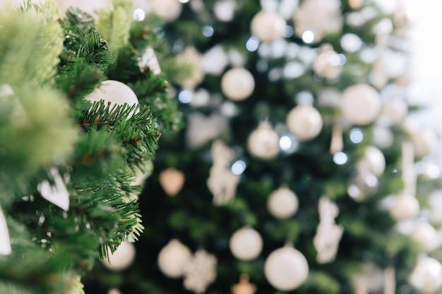 Árbol de navidad artificial, luces y decoraciones. juguetes de navidad. fondo desenfocado borroso.