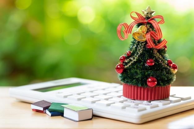 Un árbol de navidad bellamente decorado colocado en una calculadora blanca