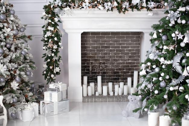Árbol de navidad con bolas, chimenea con velas y regalos en la sala de estar. el interior navideño de la habitación está decorado en colores blancos, decorado con árboles de navidad y elementos decorativos de chimenea.