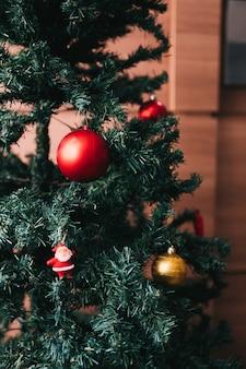 Árbol de navidad con bolas doradas y rojas y santa.