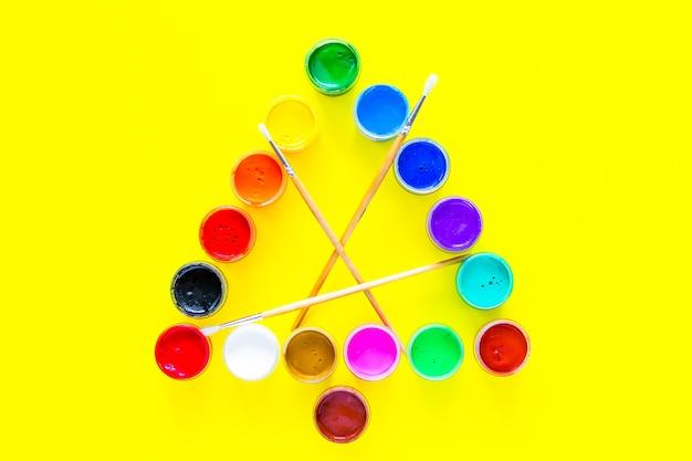 Árbol de navidad creativo hecho de latas de pintura con borlas en el centro sobre un fondo amarillo vista superior ...
