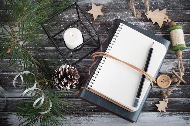 Árbol de navidad, cuaderno abierto vacío y decoración navideña