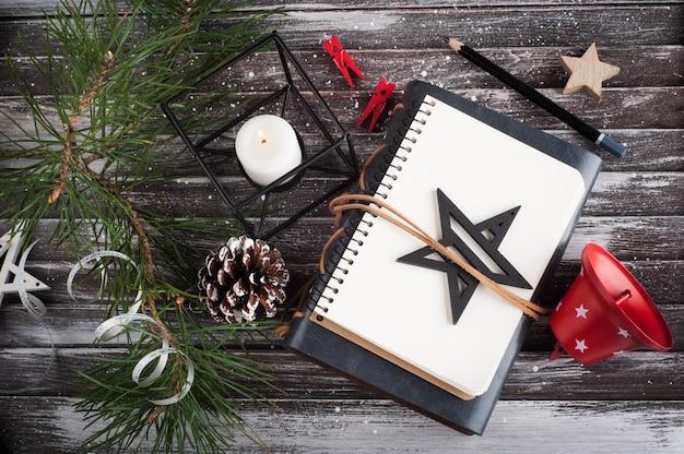 Árbol de navidad, cuaderno abierto vacío y decoración roja de navidad