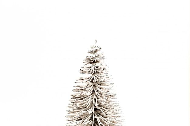 Árbol de navidad cubierto de nieve blanca sobre un blanco en el medio con copyspace para texto