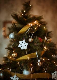 Árbol de navidad decorado con adornos dorados y blancos.