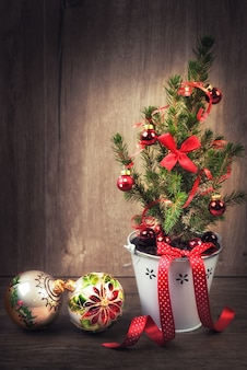 Árbol de navidad decorado y adornos rojos sobre fondo de madera