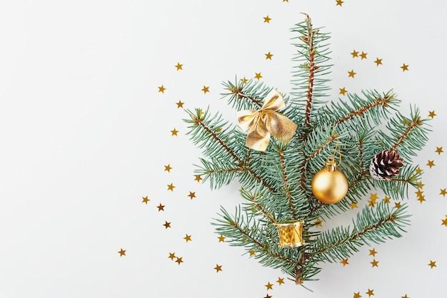 Árbol de navidad decorado con bolas de oro y juguetes de navidad sobre fondo blanco.