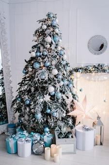 Árbol de navidad decorado con cajas de regalos en una habitación blanca.