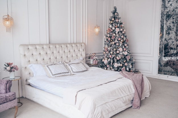 Árbol de navidad decorado en interior de dormitorio clásico blanco