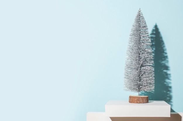 Árbol de navidad decorativo sobre un fondo azul. sombras duras.