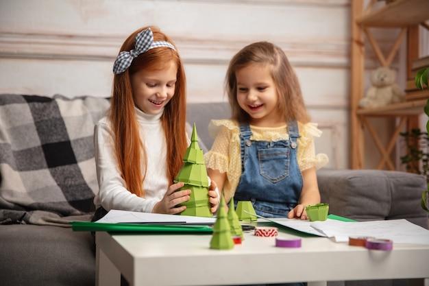 Árbol de navidad. dos niños pequeños, niñas juntas en creatividad. los niños felices hacen juguetes hechos a mano para juegos o celebración de año nuevo. pequeños modelos caucásicos. infancia feliz, preparación para la celebración.