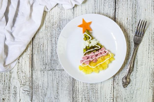 Árbol de navidad de una ensalada más olivier en placa sobre una mesa de madera blanca. vista superior con un espacio de copia
