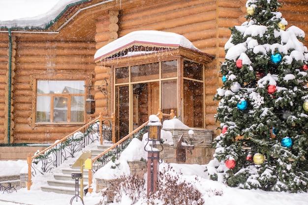 Árbol de navidad en la entrada de una casa de madera en la nieve.