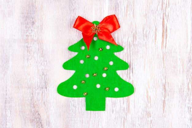 Un árbol de navidad de fieltro hecho a mano con juguetes de cuentas doradas y un lazo rojo en la parte superior descansa sobre una mesa de madera