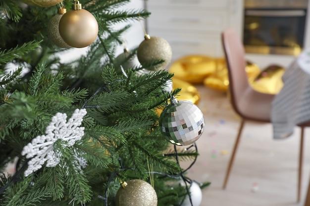 Árbol de navidad en la habitación desordenada después de la celebración de la fiesta de año nuevo