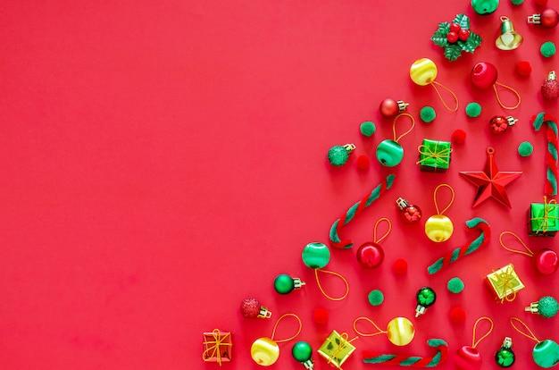 Árbol de navidad hecho de adornos de año nuevo sobre fondo rojo. flat lay minimal holiday.